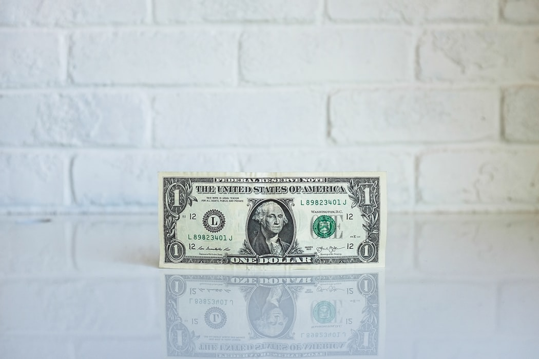 A dollar bill on a white surface.