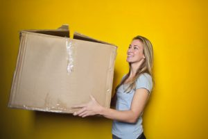 a woman holding a large moving boxes