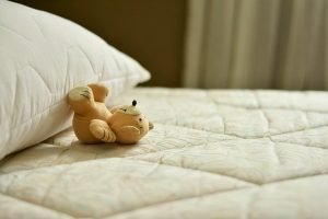A mattress and a teddy bear