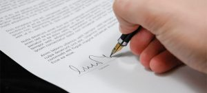 A person signing a document after learning the things to know about moving contracts.