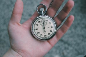 a hand holding a pocket clock