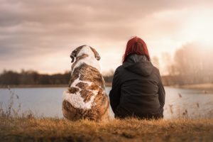 A girl and her dog sitting by a lake