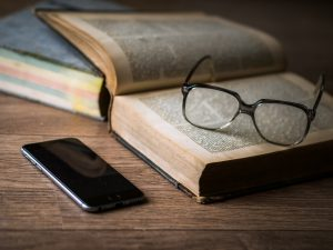 glasses, book and a phone on the table