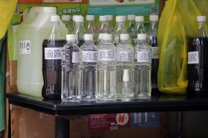 bottles of several sizes with several different liquids on a table