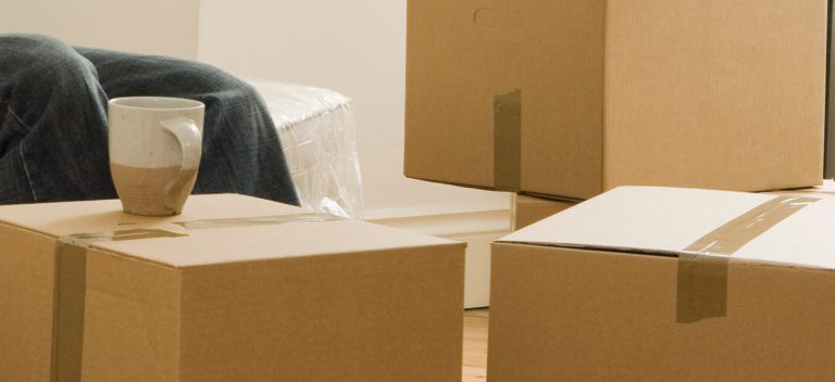 A man sitting next to moving boxes