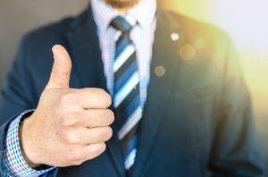 Man in a suit with a thumb up