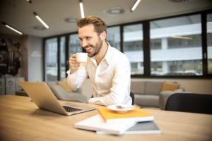 Man on his laptop in an office drinking coffee