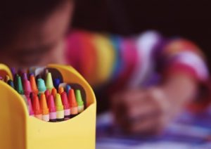 zoomed crayons and a blury child in the background