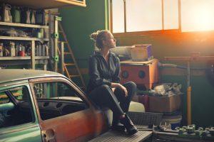A woman sitting on a car in a garage