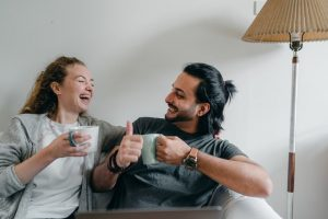two people laughing and drinking coffee, wondering should you rate your movers after the relocation?