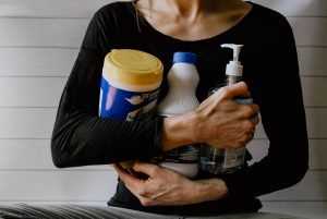 A woman holding bottles for cleaning
