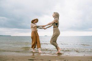 two women dancing on the beach