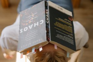Book called Chaos on a persons head