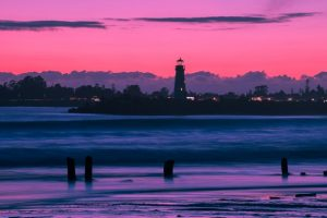 Purple sunset and a lighthouse you can enjoy in after moving to California in 2020