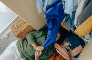 person under a pile of clothes