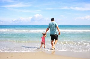 a father walking with his daughter on the beach