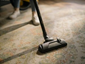 person vacuuming a rug