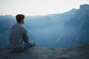 A man sitting and thinking on a cliff