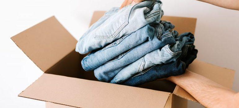crop-man-packing-casual-clothes-into-carton-box