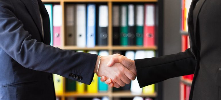 Two people in suits shaking hands in an office.