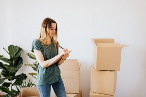 boxes and a woman writing a plan on how to reduce waste during your long-distance move
