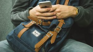 a man holding a phone - Pack your essentials bag