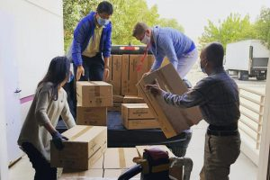 A moving team working together to load moving boxes.