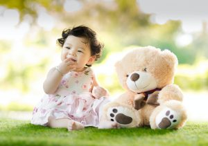 little girl and teddy bear after you declutter your kid's toys before moving