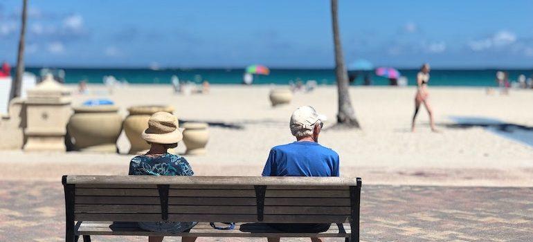 elderly couple on bench on a beach