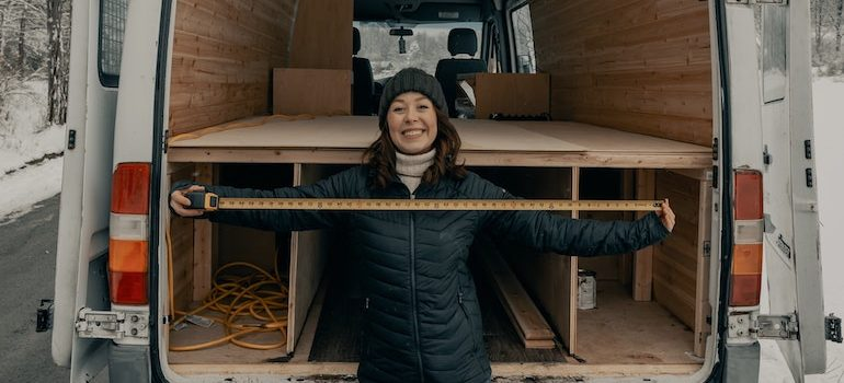 a woman standing in front of the moving truck with a measuring tape