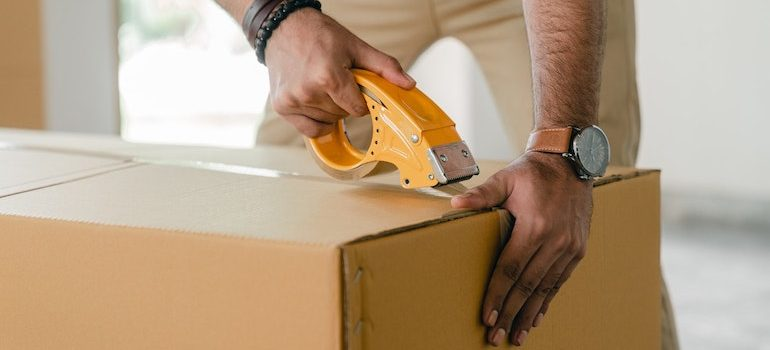 man sealing a box with duct tape