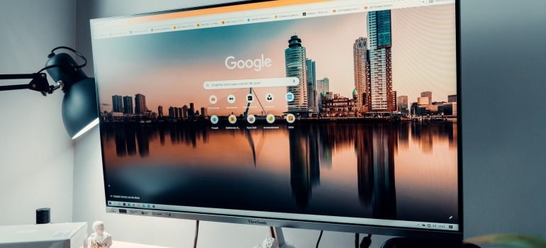 Big computer screen with shown picture of a city and icons of Google, standing on desk and against the grey wall, with a lamp on the left side