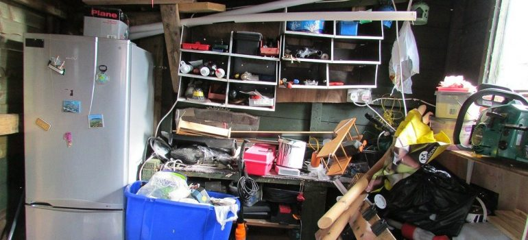 a messy room cluttered with various things, an overloaded shelf on the wall and a refrigerator with magnetic pictures