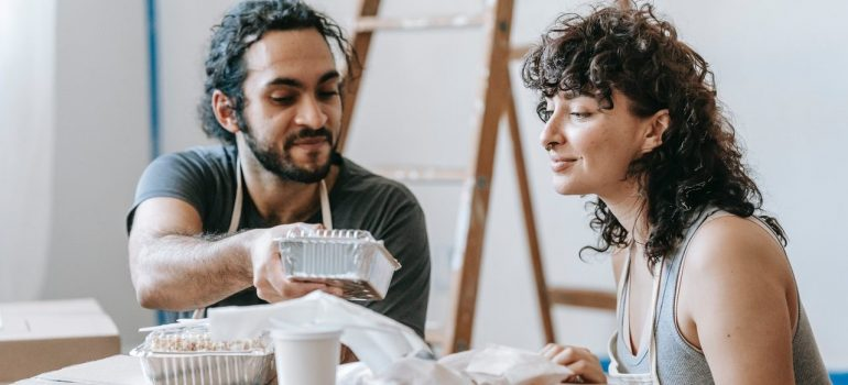 a man and woman are sitting and eating delivery food
