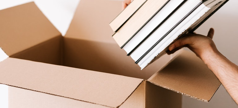 Person packing stacks of books in carton box