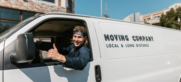 Man in black clothes seating in a white van with inscription has timely arrived to make your movers cost per hour lower and is in front of the house