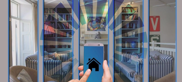a man holds a mobile phone with a house icon and looks through a glass wall inside the house