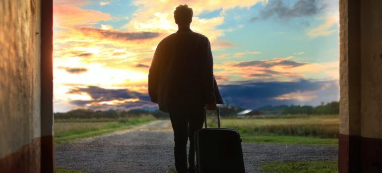 A male figure with a suitcase on the move