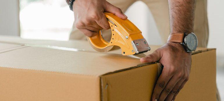 person sealing a cardboard box