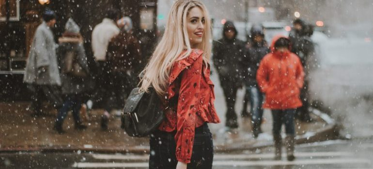A woman on a street while it snows
