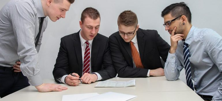 A group of 4 men looking at documents