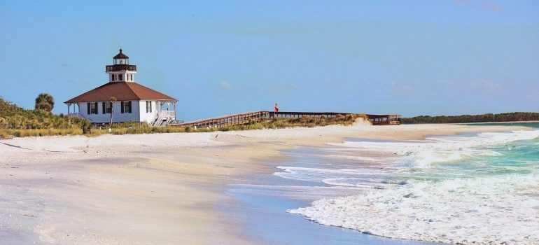 Sandy beach, waves on the water and in the distance a lighthouse and a person walking over the pier.