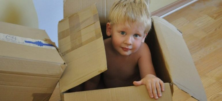 A boy sitting in a cardboard box to representing moving from Kendall to Pompano Beach