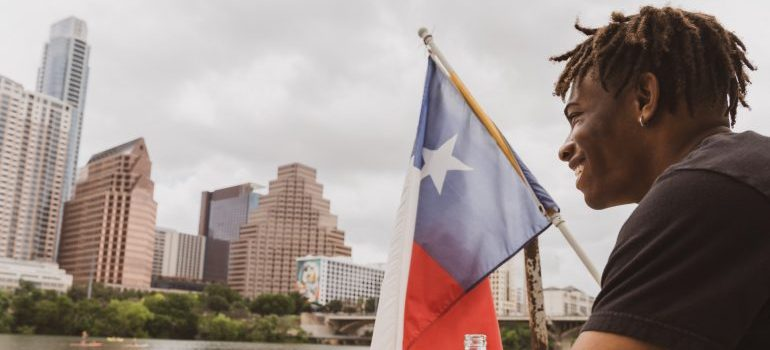 A man next to the TX state flag - moving to Texas from Florida