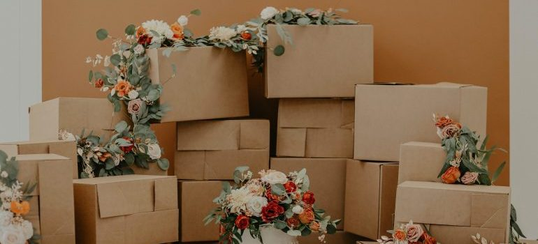A lot of cardboard boxes stacked on top of one another, some covered with flowers representing the process of moving