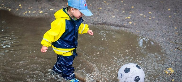 A boy playing with a ball while jumping in a puddle
