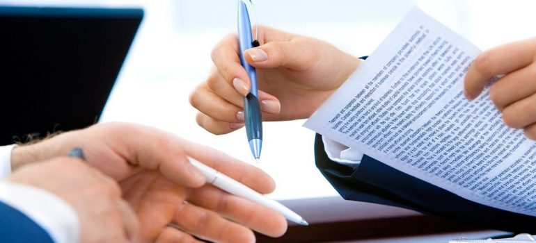 Two hands holding pens and papers with typed letters, preparing to sign them.
