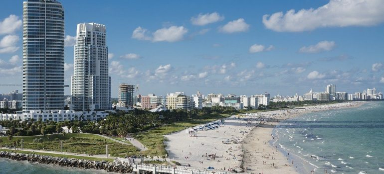 A scene of Miami during the daytime, with a pier, waterfront, high condo buildings close to beach, and people on the beach who decided to come to Miami after considering living in Florida vs California.