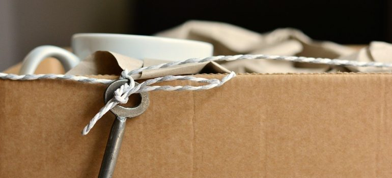 The rim of a cardboard box with a key on a string, a mug and a cloth peeking out from it