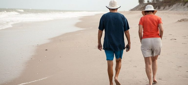 Man and woman with T-shirts, shorts, white hats and walking barefoot on the sandy beach with ocean on the left side.